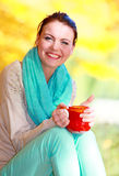 Happy girl relaxing in the autumn park enjoying hot drink Royalty Free Stock Photography