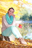 Happy girl relaxing in the autumn park enjoying hot drink Royalty Free Stock Photo