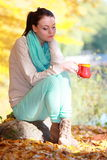 Happy girl relaxing in the autumn park enjoying hot drink Stock Photos