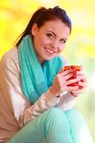 Happy girl relaxing in the autumn park enjoying hot drink Stock Photo