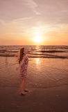 Happy girl relaxing on beautiful beach at sunset. Stock Image