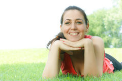 Happy girl relaxing on green grass Royalty Free Stock Images
