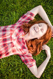 Happy girl relaxing on green grass. Royalty Free Stock Photos