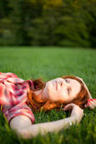 Happy girl relaxing on green grass. Royalty Free Stock Image