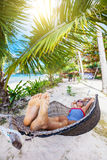 Happy girl relaxing on a tropical beach in hammock. Royalty Free Stock Photo