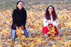 Happy girl relaxing on yellow autumn leaves. Happy family playing against blurred autumn leaves background stock images