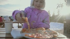 The girl is having lunch. Happy girl in the middle of snowy mountains. Winter holidays. Happy girl resting and having lunch at a winter resort in the midst of stock video footage
