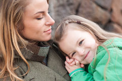 Happy girl resting on mom's shoulder Royalty Free Stock Images