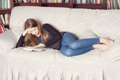 Happy Girl Resting on Sofa at the Living Room While Reading Royalty Free Stock Photo