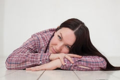 Happy girl rests on wooden floow and smiles. Girl with long hair lying on the white floor and resting, smiling Stock Photos