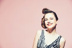 Happy girl with with retro hair and fashionable makeup, pinup. Happy girl in stylish vintage dress on pink background with with retro hair and fashionable makeup royalty free stock photos
