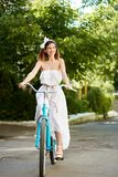 Happy girl rides on retro bicycle against background green plantings. Happy girl in a summer dress rides on a blue retro bicycle against a background of green Stock Image