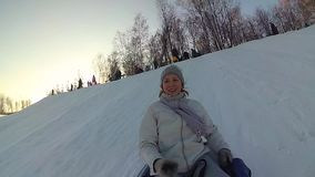 Happy girl rides and smiling snowtube on snowy roads. slow motion. snow winter landscape. outdoors sports stock video