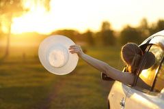 Happy girl rides into the sunset in the car. Stock Photography