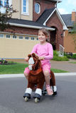 Happy girl rides at toy horse near cottage Stock Photos