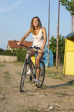 Happy girl riding bicycle on the clay running track Stock Photo