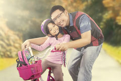 Happy girl riding a bike with dad Royalty Free Stock Photo