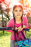 Happy girl riding a bike Stock Images