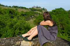 Happy girl on rock relaxing with a view to grape field landcape and the Festung or fort Marienberg in background. A happy girl on rock relaxing with a view to Stock Photography