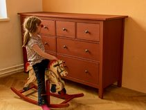 Happy girl on rocking horse. Little girl wears red glasses. stock photography
