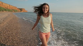Happy girl running along the beach barefoot and