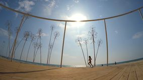 Happy Girl Running Along Beach With Futuristic Dandelions At Befooz. Happy girl is running along sandy beach at famous musical festival Befooz with bunches of stock video footage