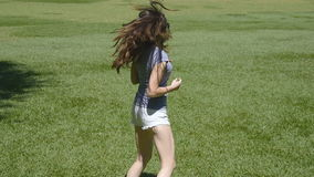 Happy girl is running along green grass in the countryside and raising hands. Young beautiful woman jogging and spinning stock video