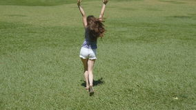 Happy girl is running along green grass in the countryside and raising hands. Young beautiful woman jogging and spinning stock video footage