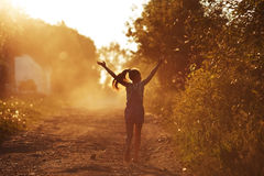 Happy girl running on a dusty road Stock Photos