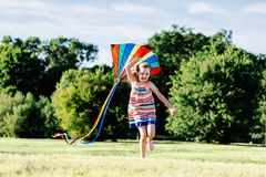 Happy girl running on the grass field with a colorful kite. Royalty Free Stock Images
