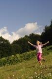 Happy girl running on meadow. Stock Photos