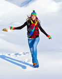 Happy girl running in the snow. Teen outdoor winter activities, female having fun at Christmastime, woman wearing colorful clothes, freedom and nature joy Royalty Free Stock Photo