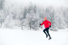 Happy girl running on snow in winter mountains. royalty free stock images
