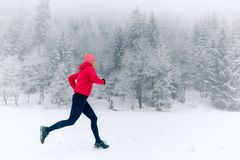 Happy girl running on snow in winter mountains. Sport, fitness inspiration and motivation. Young happy woman trail running in stock photo