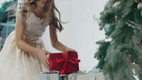 Happy girl taking present box near christmas tree in modern apartment. Happy girl running to christmas tree in private house. Portrait of happy girl taking stock video