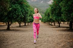 Happy girl running to the new life in the morning. Ready to achieve a new targets.Conception of the healthy lifestyle stock image