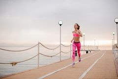 Happy girl running to the new life on the sunrise. Ready to achieve a new goal.Conception of the healthy lifestyle royalty free stock photography