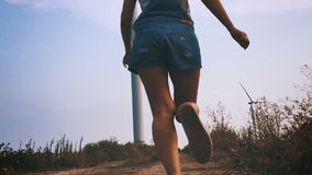 Happy girl running towards the wind turbine, slow motion. stock video