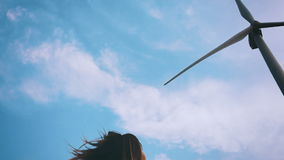 Happy girl running towards the wind turbine, slow motion. stock video footage
