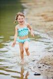 Happy girl running through water on beach Royalty Free Stock Photos