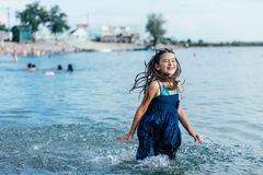 Happy girl running through the water stock images