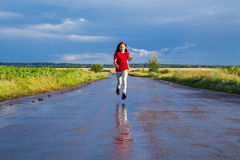 Happy girl running on wet road. After rain Stock Photos