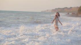 Happy girl runs along the beach and enjoys stock video footage