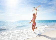 Happy girl runs at the beach and holds toy plane. Portrait of happy little girl in swimsuit holding toy plane and running on the beach at sunny day Royalty Free Stock Images
