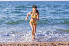 Happy girl runs from the sea Stock Image