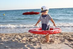 Happy girl in sailor hat on beach Stock Photo