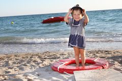 Happy girl in sailor hat on beach Stock Images