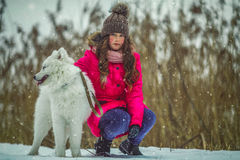 Happy girl with Samoyed dog in winter forest Stock Photography