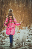 Happy girl with Samoyed dog in winter forest Stock Image