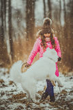 Happy girl with Samoyed dog in winter forest Royalty Free Stock Images